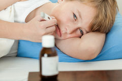 Boy using thermometer with medicine bottle nearby Royalty Free Stock Image