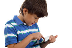 Boy using touch screen tablet. A young boy uses a touch screen tablet to play games - on white background - close crop - copy space to right Royalty Free Stock Photography