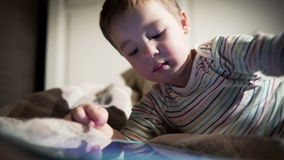 Boy using touchpad. Little boy using touchpad and scrolling something there lying on the bed stock video