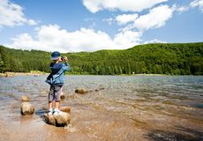 Boy using video camera outdoors. Boy filming the beautiful landscape with a lake and pine forest Stock Photos