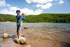 Boy using video camera outdoors. Boy filming the beautiful landscape with a lake and pine forest Stock Image