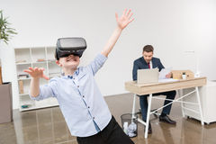 Boy using virtual reality glasses while his father businessman royalty free stock image