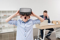 Boy using virtual reality glasses while his father businessman stock image