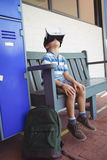 Boy using virtual reality glasses while sitting on bench. In corridor at school Royalty Free Stock Photos