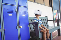 Boy using virtual reality glasses while sitting on bench by lockers. In corridor at school Royalty Free Stock Images