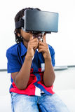 Boy using virtual reality headset in classroom. Elementary boy using virtual reality headset while sitting in classroom Stock Images