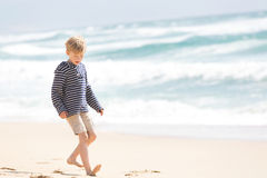 Boy at vacation. Positive happy boy walking at the beach being active and playful at the beach Stock Photos