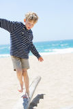 Boy at vacation. Positive happy boy walking on the old trunk at the beach being active and playful at the beach Royalty Free Stock Images
