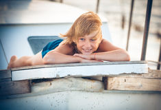 Boy vacationer by the boat royalty free stock photography