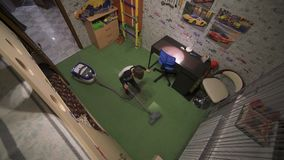 The boy is vacuuming in the room. Helps parents on home affairs. Top view. 4K stock video