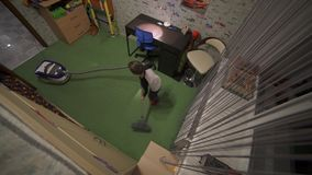 The boy is vacuuming in the room. Helps parents on home affairs. Top view. 4K stock video footage