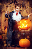 Boy vampire. Cute boy in a costume of vampire posing in a wooden barn with pumpkins. Halloween holiday stock photography