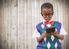 Boy in vest and bowtie with calculator against blurry wood panel Royalty Free Stock Photos