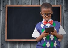 Boy in vest and bowtie with calculator against chalkboard and grey wood panel Royalty Free Stock Image