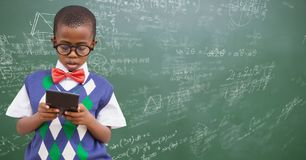 Boy in vest and bowtie with calculator against green chalkboard with math doodles Royalty Free Stock Photography