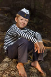 The boy in the vest and the marine cap. The boy in the striped vest with cap in stone royalty free stock photography
