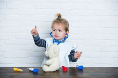Boy veterinarian doctor with toy teddy bear point finger. On white wall. Future profession concept. Health, healthcare, medicine. Game, development, imagination stock photo