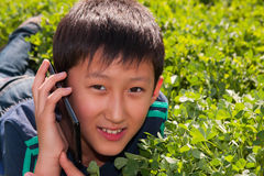 Boy via sellphone. Teenager boy lying on the grass and speaking via sellphone Royalty Free Stock Images