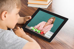Boy Videoconferencing On Digital Tablet. Close-up Of Cute Little Boy Videoconferencing On Digital Tablet In Classroom Stock Photo