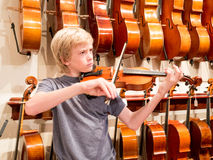 Boy Violinist Playing A Violin In A Music Store Stock Photography