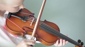 Boy violinist plays the violin at home. Smart boy rehearsing a melody on a creep stock footage