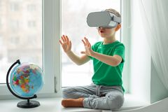 A boy with a virtual reality headset is sitting at home at the table indoors. The child explores the world of virtual reality. Through video and games royalty free stock photo