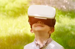 Boy in a virtual reality helmet on a background of green grass Stock Images
