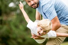 Boy with vitality laughing with joy. Playing with father at the park Royalty Free Stock Image
