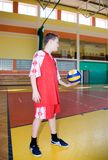 A boy with a volleyball. A young volleyball player with a ball, standing alone in a gym, practising his serving. MORE SPORT IMAGES royalty free stock image