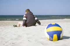 Boy with volleyball on beach stock photos