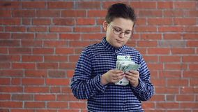 A boy with a wad of money in his hands stock video footage