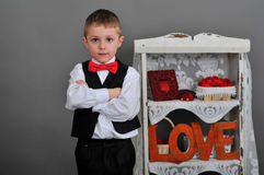 Boy in waistcoat and bow tie. Boy in vest, red bow tie. next to the inscription love Royalty Free Stock Images