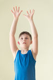 A boy waiting for ball. A boy playing volleyball, holding his arms up Royalty Free Stock Image