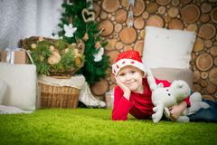 Cute boy in santa hat. Boy waiting for a holiday in a room decorated before Christmas. boy in a red sweater sits on a green carpet Royalty Free Stock Photography