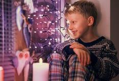 Boy waiting Santa on the window with Christmas Lights Royalty Free Stock Image