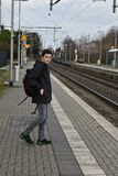 Boy waiting for the train. Teenage boy standing on platform at station waiting for the  train Royalty Free Stock Photos
