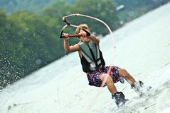 Boy on Wakeboard Losing Control. A young boy on a wakeboard has lost control and is about to fall. 9 years old royalty free stock images