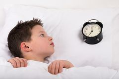 The boy wakes up in bed and looks at the big clock. The boy wakes up in bed and  looks at the big clock Stock Photos