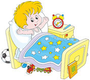 Boy waking up. Little boy waking up and stretching in his bed at home Royalty Free Stock Photography