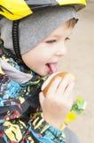 A boy on a walk eats a cake, a smiley face, Stock Photography