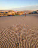 Boy walking across Sand Dune stock photo