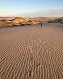 Boy walking across Sand Dune Stock Photo
