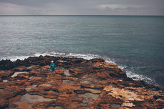 Boy is walking alone on the seashore. Seashore with blue water. Teenage is exploring coast Stock Image