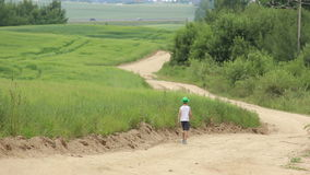 Boy walking along a country sand road near the field stock footage