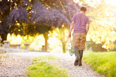 Boy Walking Along Path Carrying Fishing Net And Jar Royalty Free Stock Images