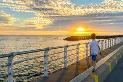 Boy walking along St. Kilda Jetty. At sunset, Melbourne, Victoria, Australia Royalty Free Stock Photos