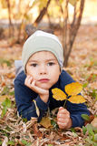 Boy walking in autumnal park Stock Photos