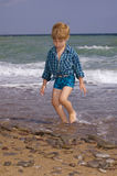 Boy walking on the beach Royalty Free Stock Photos