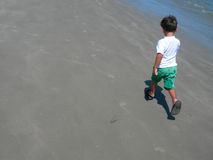 Boy walking on beach. Angled rear view of young boy walking on sandy beach with sea in background Stock Photos