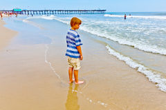 Boy walking on the beach Stock Images